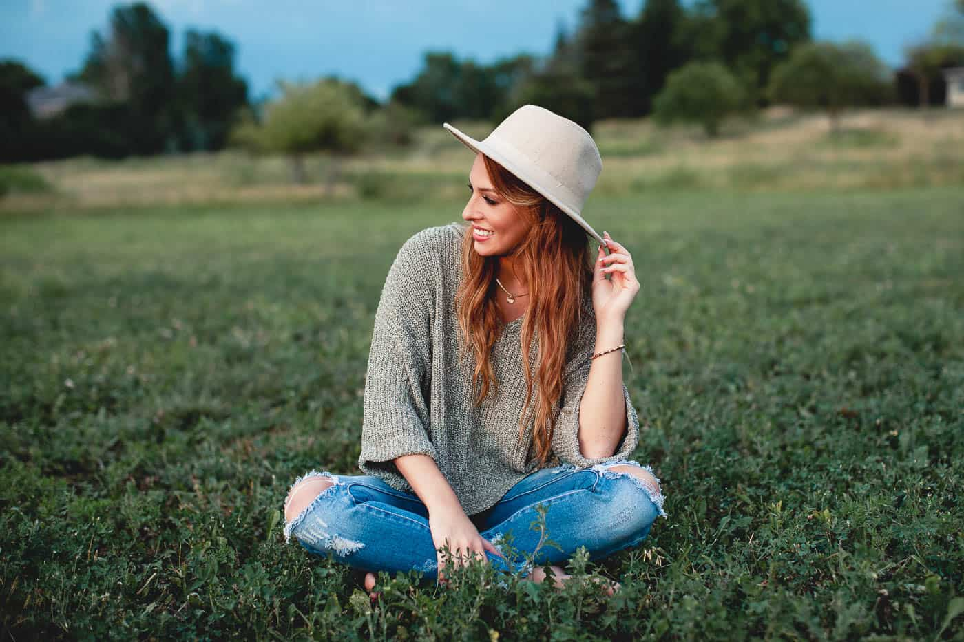 senior girl chillin in a field with a hat on for her senior session