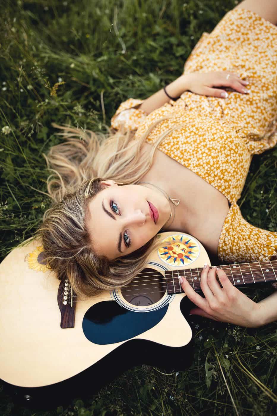 portrait of senior girl lying with her guitar
