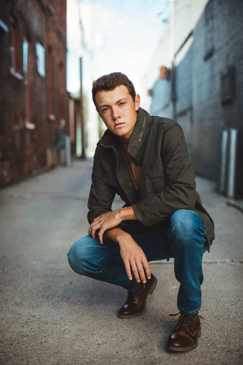 Guys Green Bay Wisconsin senior portraits taken downtown with an urban styled green army coat