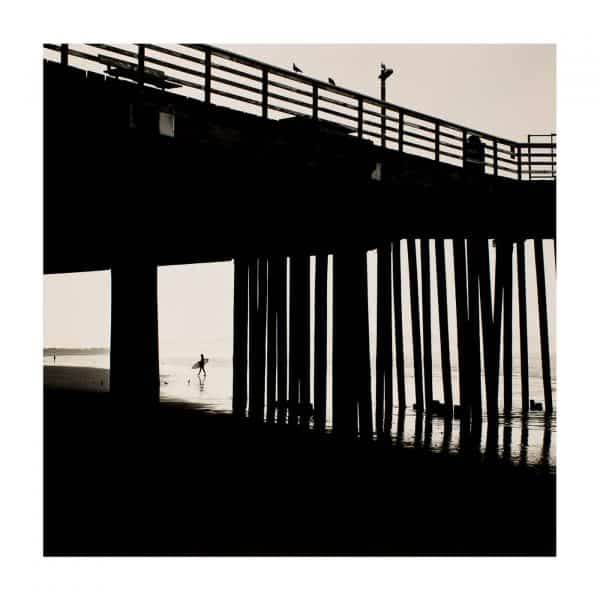 Surfer and pier at Pismo Beach California